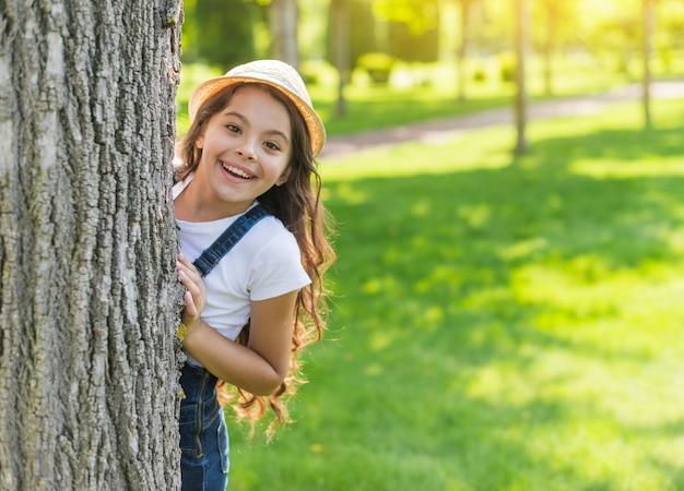 Menina sorridente, escondendo-se atrás de uma árvore