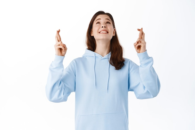 Menina sorridente esperançosa olhando para cima enquanto faz um desejo, cruze os dedos para dar boa sorte, rezando para que deus passe no exame, implorando pela realização de um sonho, de pé contra uma parede branca