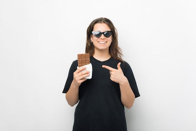 Menina sorridente está apontando para uma barra de chocolate.