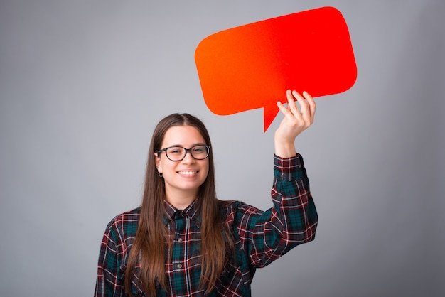 Menina sorridente está segurando um discurso vermelho bolha cinza