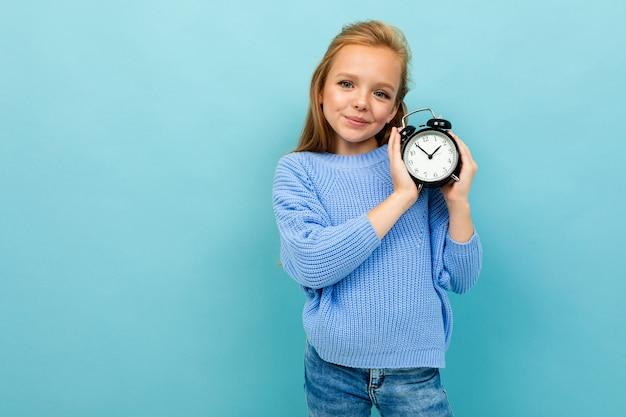 Menina sorridente europeu, segurando um despertador nas mãos de uma luz azul com copyspace