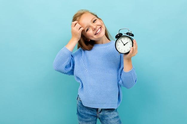 Menina sorridente europeu, segurando um despertador nas mãos de uma parede de azul claro