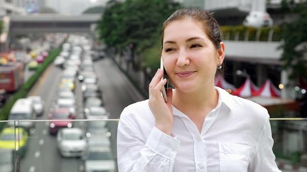 Menina sorridente falando no smartphone em pé na ponte em close-up copyspace