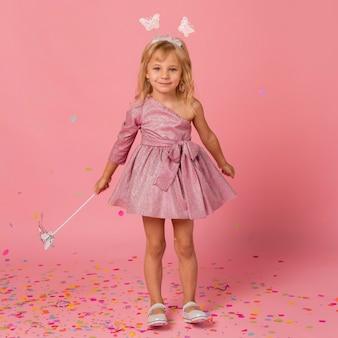 Menina sorridente fantasiada de fada com confete e varinha