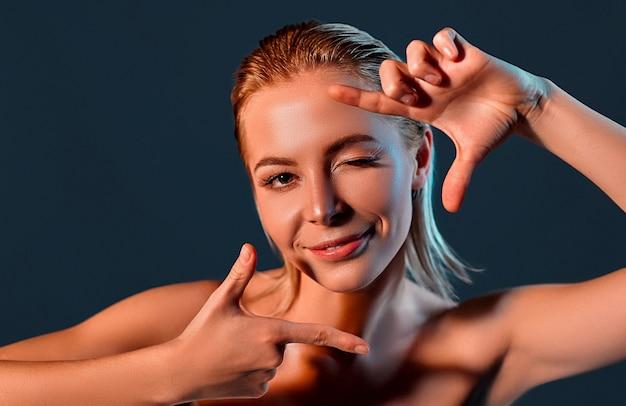 Menina sorridente faz moldura dos dedos perto do rosto.