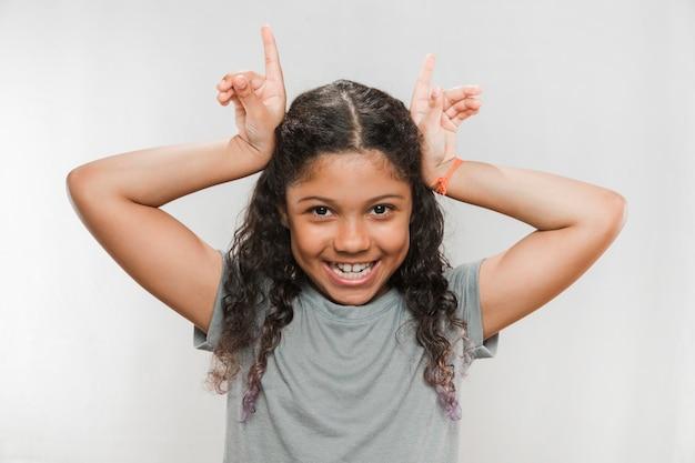 Menina sorridente fazendo gesto de chifre contra fundo branco