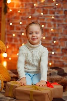 Menina sorridente feliz com caixa de presente de natal.