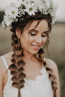 Menina sorridente feliz com tranças e guirlanda floral em vestido branco no estilo boho no verão ao ar livre