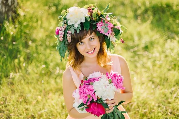 Menina sorridente feliz com uma coroa de flores e um buquê de peônias em um dia ensolarado de verão