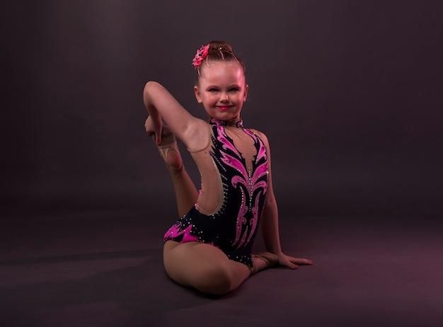 Menina sorridente feliz na ginasta fantasiada, sentada em posição no estúdio, tentando fazer o círculo com a perna e o braço.