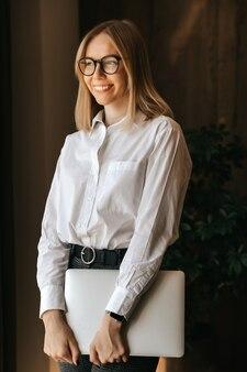 Menina sorridente fica com um laptop nas mãos no escritório.