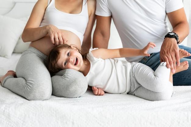 Menina sorridente, ficar na cama com os pais dela