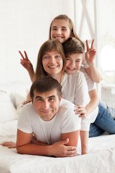 Menina sorridente, gesticulando sinal de vitória na cama com seu pai e irmão