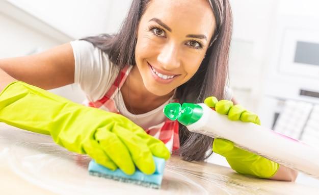 Menina sorridente, inclinada sobre a mesa sendo limpa por um detergente e uma esponja, com luvas de borracha, olhando para a câmera.