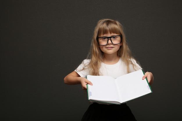 Menina sorridente inteligente linda criança bonita em copos com um livro nas mãos mostra o conteúdo.