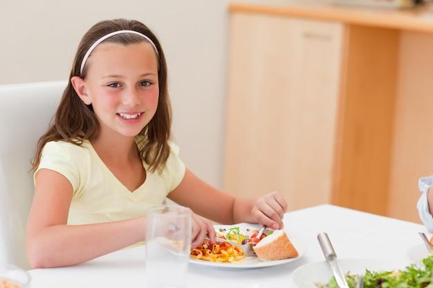 Menina sorridente, jantar na mesa de jantar
