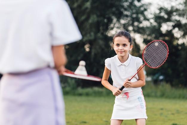 Menina sorridente, jogando badminton, com, dela, amigo