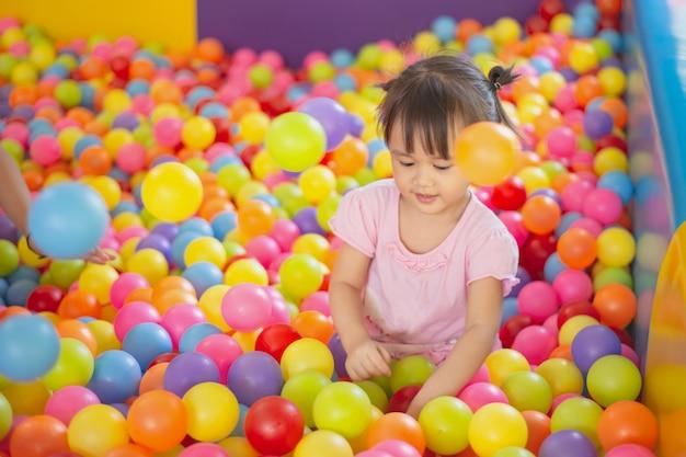 Menina sorridente, jogando na piscina de bolas