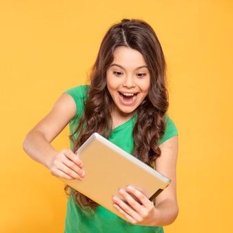 Menina sorridente, jogando no tablet