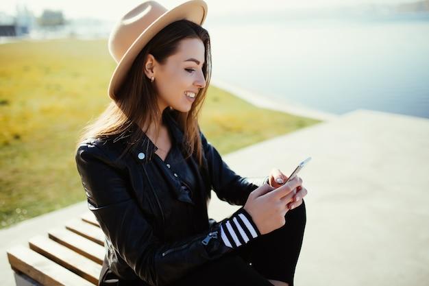 Menina sorridente jovem sentada no parque perto do lago da cidade em um dia frio e ensolarado de verão, vestida com roupas pretas