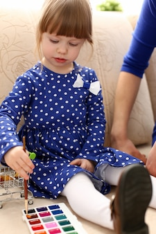 Menina sorridente loira segurar na escova do braço