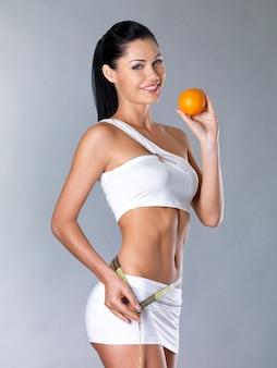 Menina sorridente mede a figura com uma fita métrica e segurando a laranja. cocnept estilo de vida saudável.