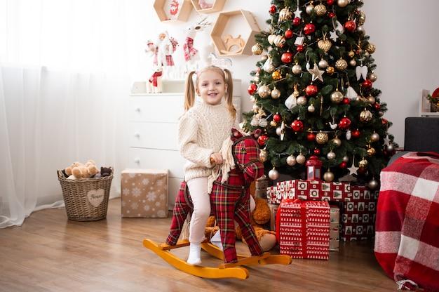 Menina sorridente, montando o cavalo de brinquedo em casa perto de caixas de árvore e presente de natal