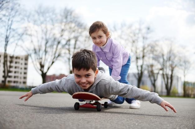 Menina sorridente montando o irmão em um skate de madeira, desfrutando de um jogo juntos em um campo de esportes