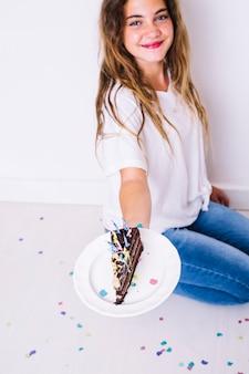 Menina sorridente, mostrando a fatia de bolo de chocolate