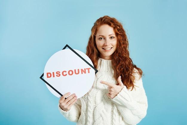 Menina sorridente mostrando banner de venda