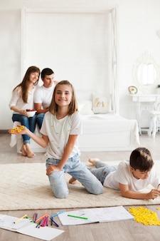 Menina sorridente, mostrando, bloco, de, scrabble, jogo, letra, enquanto, dela, pais, sentar-se cama