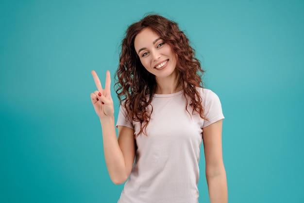 Menina sorridente, mostrando, dois dedos, isolado, sobre, experiência azul