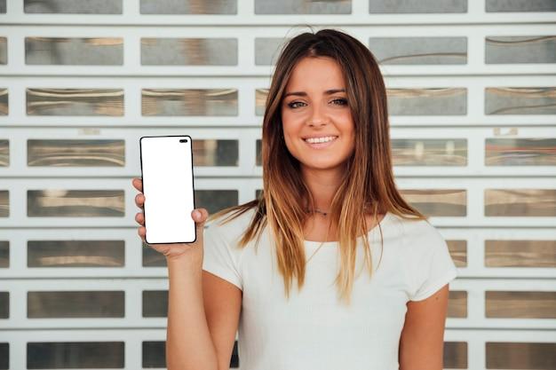 Menina sorridente, mostrando o celular com mock-up
