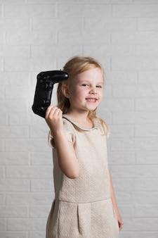 Menina sorridente mostrando para joystick de câmera