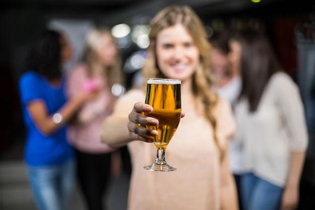 Menina sorridente, mostrando uma cerveja com as amigas