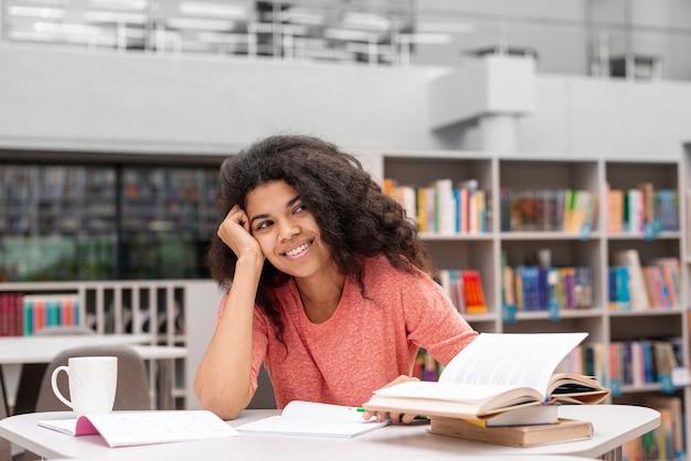 Menina sorridente na biblioteca estudando