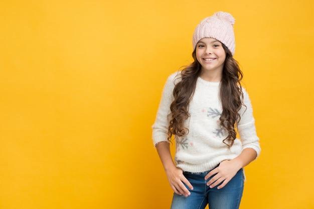 Menina sorridente na camisola com flocos de neve