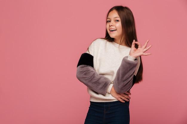 Menina sorridente na camisola, olhando e mostrando o gesto ok