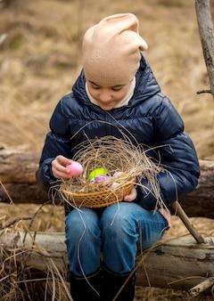 Menina sorridente na floresta olhando para ovos de páscoa coloridos na cesta