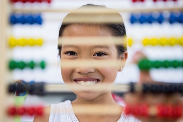 Menina sorridente na frente do ábaco na sala de aula
