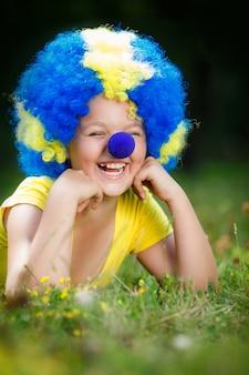 Menina sorridente na peruca de palhaço com nariz azul está deitado na grama verde no parque