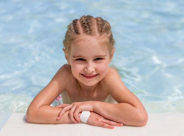 Menina sorridente nadar na beira da piscina