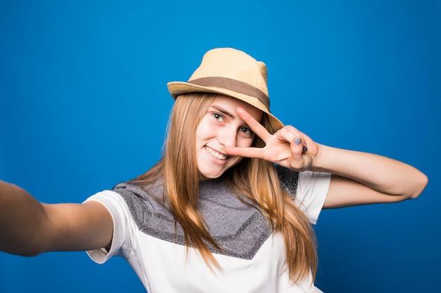 Menina sorridente no chapéu brilhante fazendo selfie em frente a parede azul