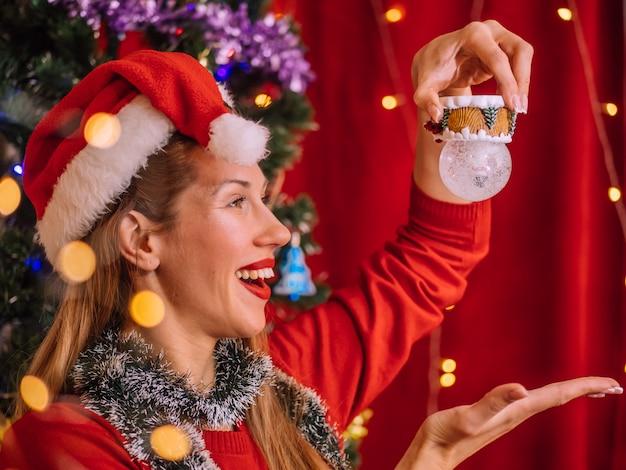 Menina sorridente no chapéu de papai noel com brinquedo. parede da árvore de natal