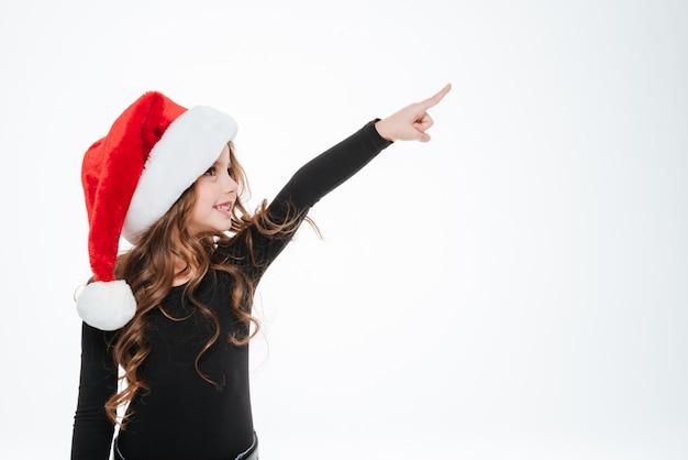Menina sorridente no chapéu de papai noel em pé e apontando para fora