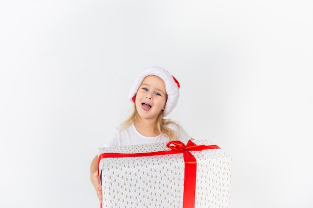 Menina sorridente no chapéu de papai noel segurando presente branco com fita vermelha