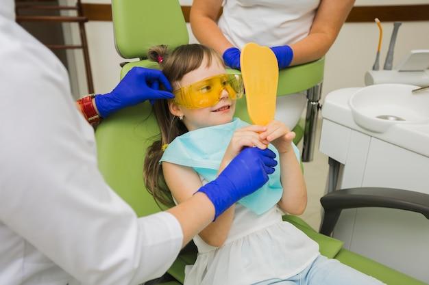 Menina sorridente no dentista olhando no espelho