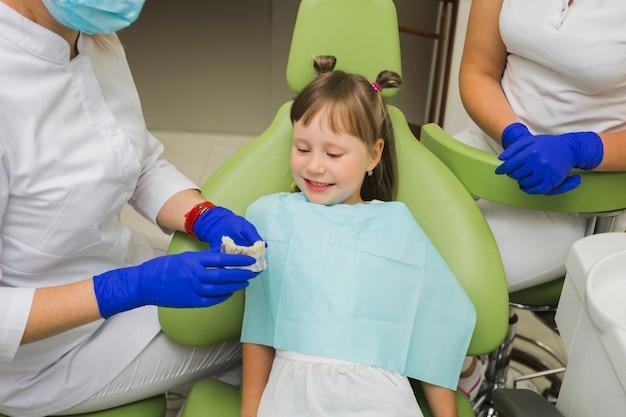 Menina sorridente no dentista olhando para dentaduras
