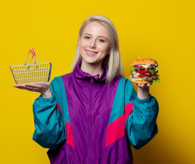 Menina sorridente no estilo de roupa dos anos 80 com cesta de hambúrguer e supermercado