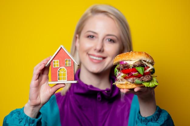Menina sorridente no estilo de roupas dos anos 80 com hambúrguer e símbolo em casa